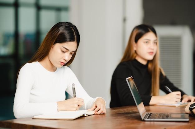 Linda aluna asiática sentada para exame em uma sala de aula universitária estudantes sentadas na fila educação estilo de vida faculdade universitária