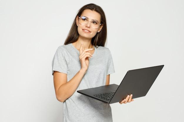 Linda aluna com roupas casuais e óculos trabalhando no laptop