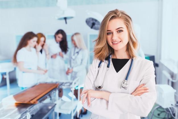 Linda aluna de medicina no fundo do grupo na sala de cirurgia