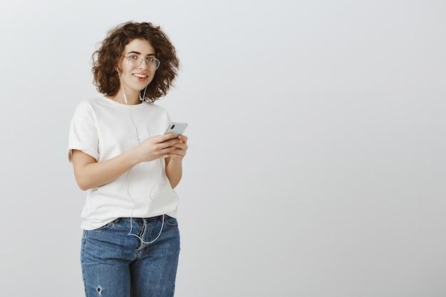Linda aluna de óculos usando smartphone e ouvindo música com fones de ouvido