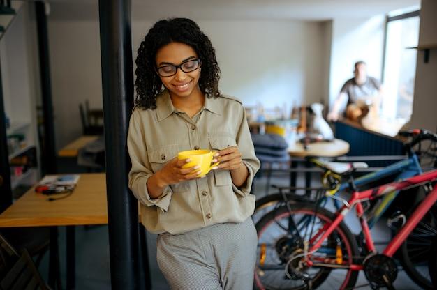 Linda aluna em copos bebe café no café. mulher aprendendo um assunto em cafeteria, educação e comida. menina estudando na cafeteria do campus