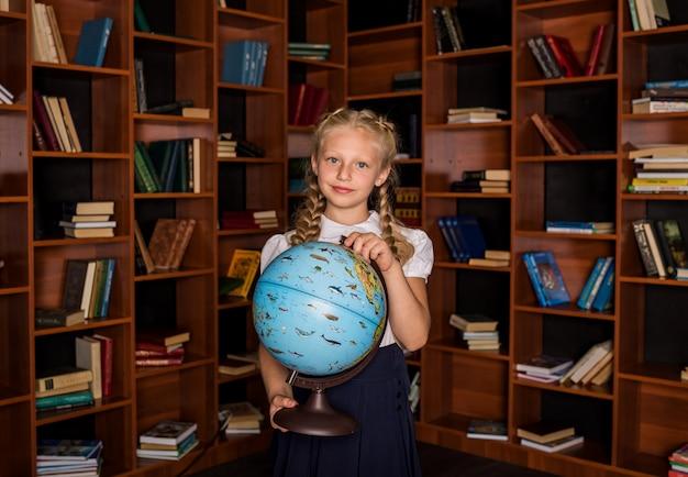 Linda aluna em uniforme escolar com um globo na sala de aula