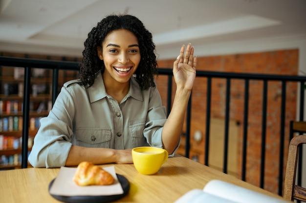 Linda aluna, leve café da manhã no café. mulher aprendendo um assunto em cafeteria, educação e comida. menina estudando na cafeteria do campus