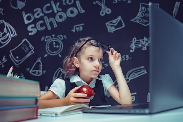 Linda aluna sentada na mesa e estudando online com o laptop contra um fundo preto