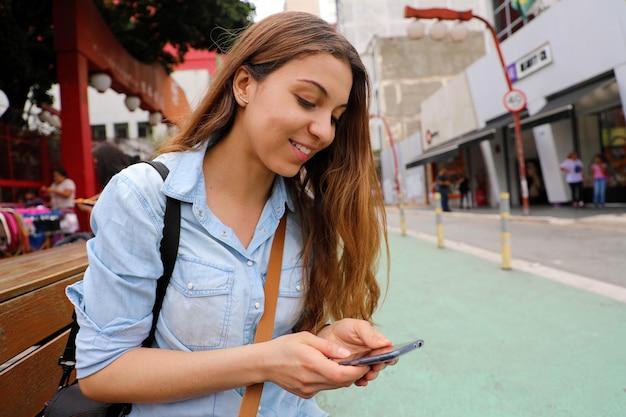 Linda aluna sentada no banco da rua, trocando mensagens com o celular na cidade de são paulo, brasil