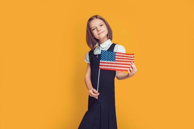 Linda aluna sorridente caucasiana segura a bandeira americana nas mãos, na bandeira dos eua de fundo amarelo
