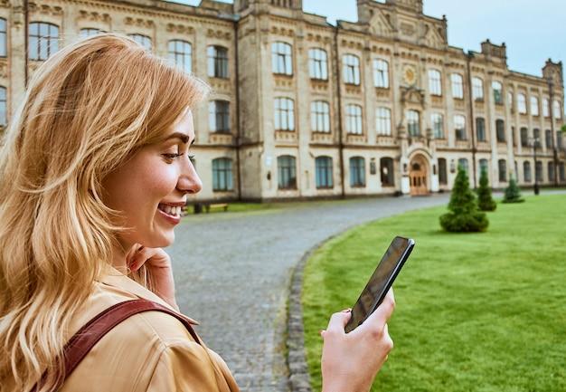 Linda aluna usa um telefone celular perto da universidade. conceito de tecnologia.