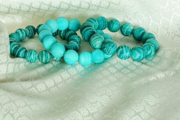 Linda amazonita ou contas de pedra da amazônia em pulseiras sobre fundo de tecido de seda tailandês