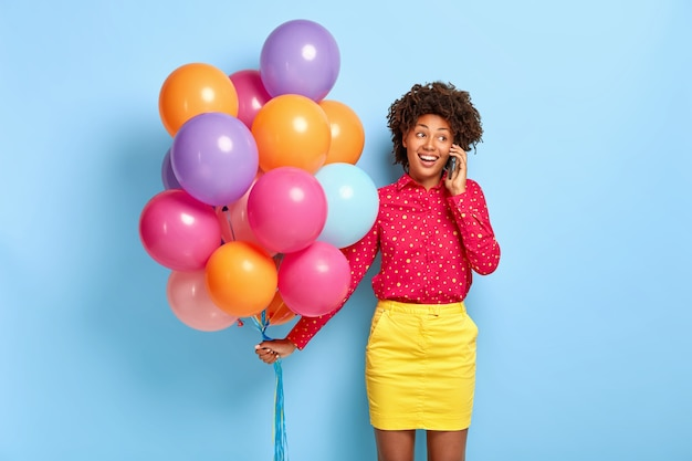 Linda aniversariante afro-americana satisfeita tem uma conversa agradável, recebe parabéns de parentes e amigos
