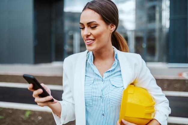 Linda arquiteta mulher caucasiana atraente em frente de sua empresa com capacete sob as axilas e usando telefone inteligente para ler e-mail.