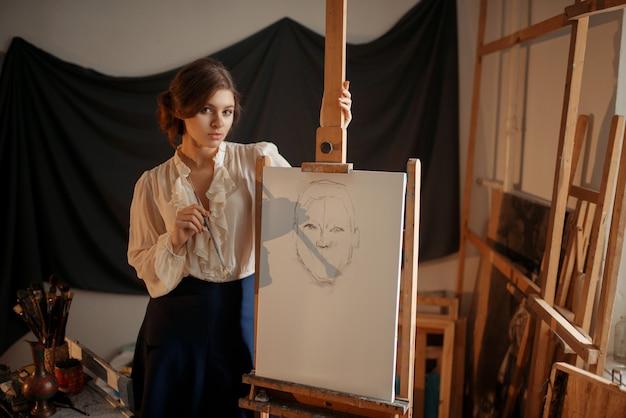 Linda artista feminina em pé contra o cavalete no estúdio.