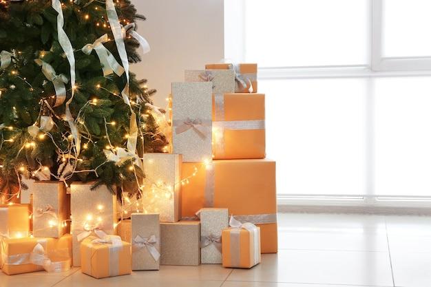 Linda árvore de natal decorada com caixas de presente na sala de estar