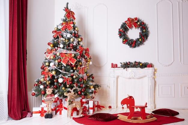 Linda árvore de natal decorada com laços e bolas dentro de casa.