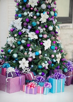 Linda árvore de natal decorada debaixo dela estão os presentes as cores principais dos brinquedos branco roxo