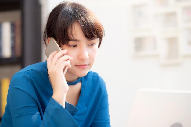 Linda asiática jovem empresária animado e feliz do trabalho de sucesso com laptop, garota tomando telefone inteligente móvel