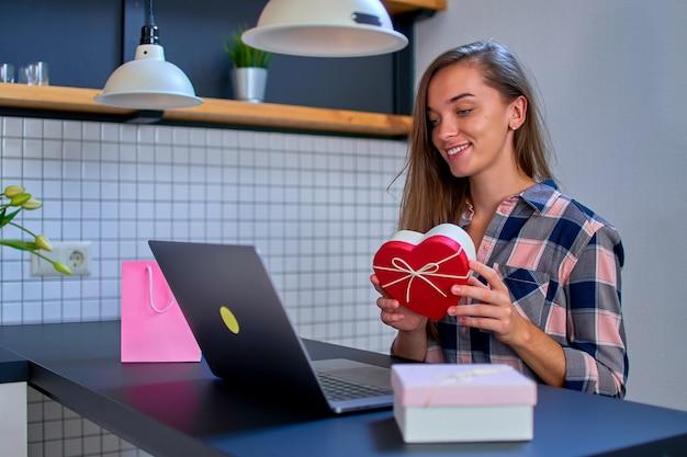 Linda atraente jovem alegre sorridente feliz mulher amada recebeu uma caixa de presente para um dia de férias e obrigado pelo presente surpresa na videochamada online em um laptop