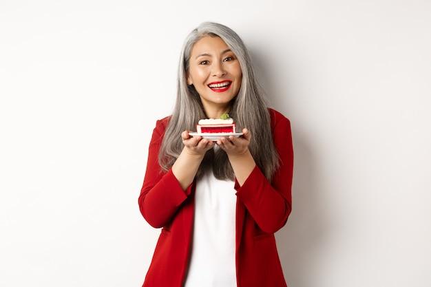 Linda avó asiática segurando um pedaço de bolo e sorrindo, de pé no blazer vermelho sobre fundo branco.