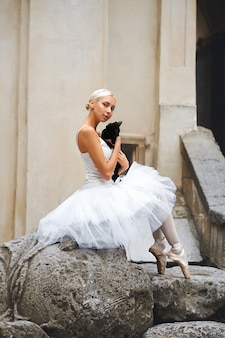 Linda bailarina acariciando gato preto