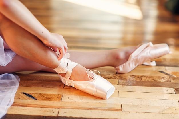 Linda bailarina amarrando sapatilhas de ponta na escola de dança.