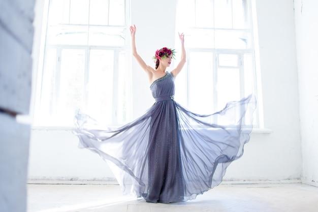 Linda bailarina dançando no vestido longo cinza