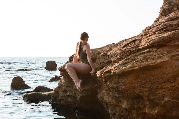 Linda bailarina dançando, posando em pedra na praia, vista para o mar.