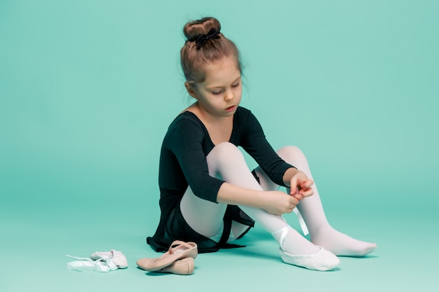 Linda bailarina de vestido preto para dançar sentado no chão e calçar sapatilhas no studio azul