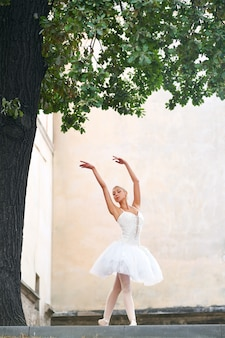 Linda bailarina graciosa dançando nas ruas de um velho ci
