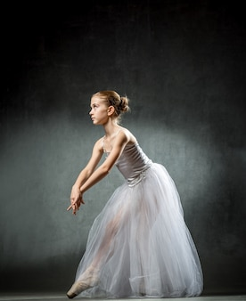 Linda bailarina jovem está dançando no estúdio em um fundo escuro. uma pequena dançarina. bailarina.