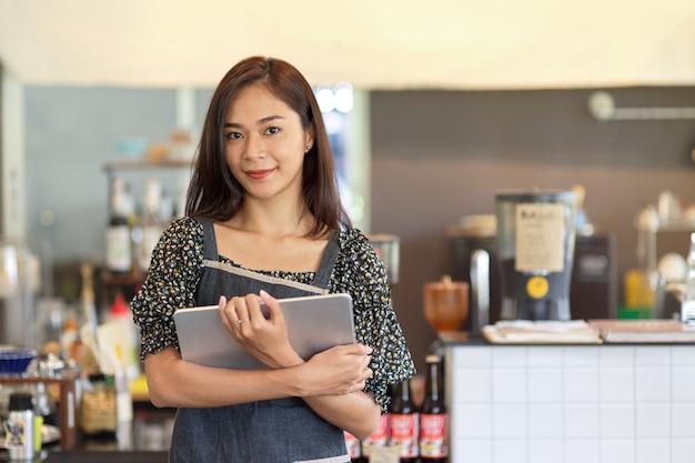 Linda barista asiática segurando um tablet digital, em frente ao balcão de uma cafeteria