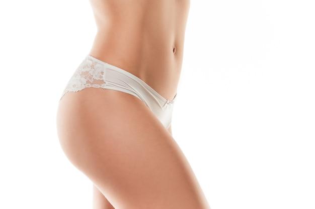 Linda barriga feminina e pernas isoladas no fundo branco