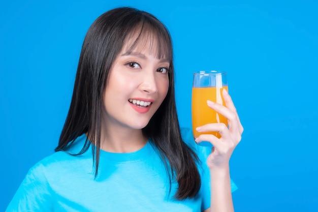 Linda beleza mulher asiática linda garota com franja estilo de cabelo em camiseta azul se sentir feliz bebendo suco de laranja para uma boa saúde em fundo azul - estilo de vida beleza mulher conceito saudável