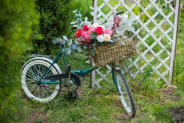 Linda bicicleta com flores em uma cesta fica em uma avenida em um parque ao pôr do sol