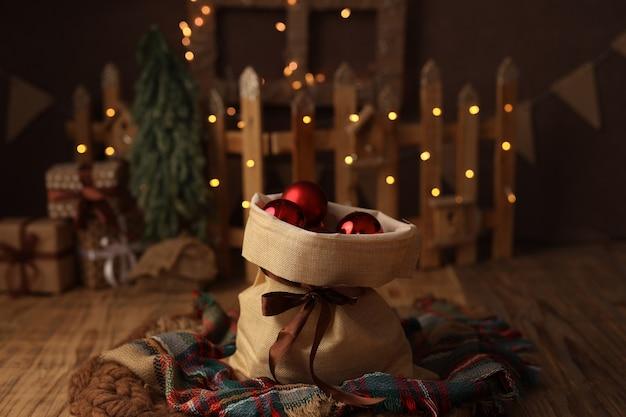 Linda bolsa de natal com presentes feitos de bolas de árvore de natal vermelhas em um fundo escuro