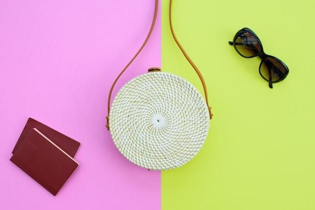 Linda bolsa de palha redonda e óculos de sol com passaportes no fundo verde-rosa. bolsa da moda.