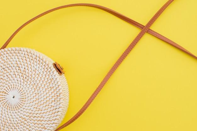 Linda bolsa de palha redonda no fundo amarelo. bolsa da moda.