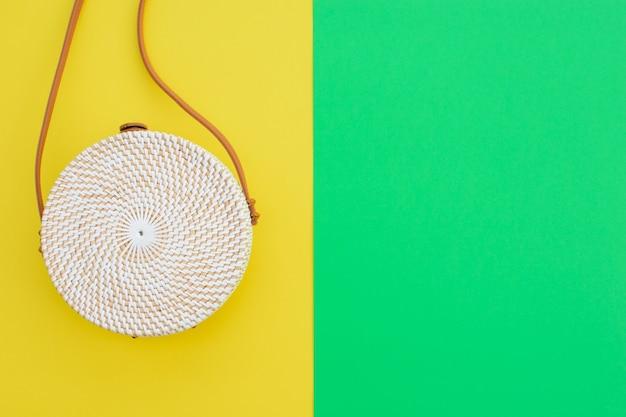 Linda bolsa redonda de palha no fundo verde-amarelo. bolsa da moda. lugar para texto.
