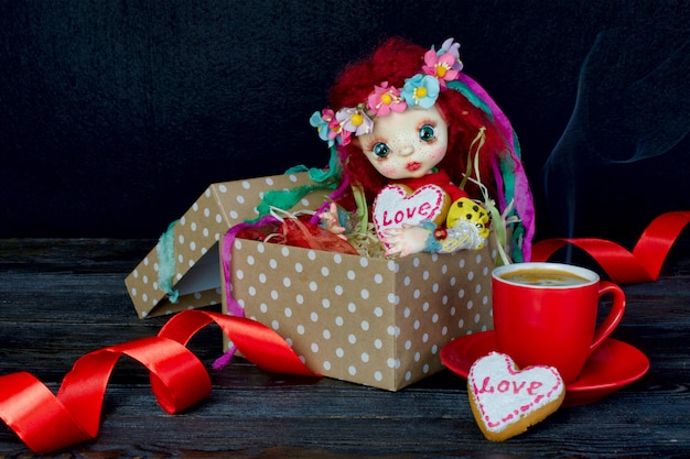Linda boneca sentada em uma caixa de presente com um coração. nas mãos de um biscoito.