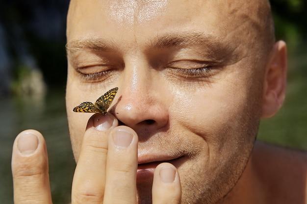Linda borboleta está sentada no nariz do homem alegre sem pêlos, ele está tocando-a com os dedos.
