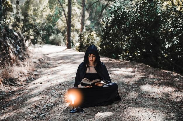 Linda bruxa lendo velho tomo na floresta na estrada