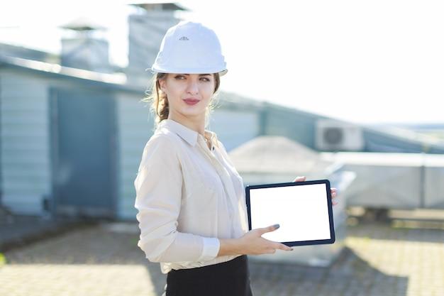 Linda businesslady na blusa branca, relógio, capacete e saia preta ficar no telhado e mostrar tablet vazio