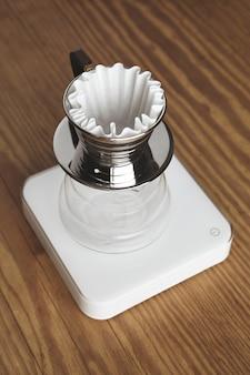Linda cafeteira transparente com copo cromado para café filtrado, apoiada em pesos brancos simples, isolada em uma mesa grossa de madeira