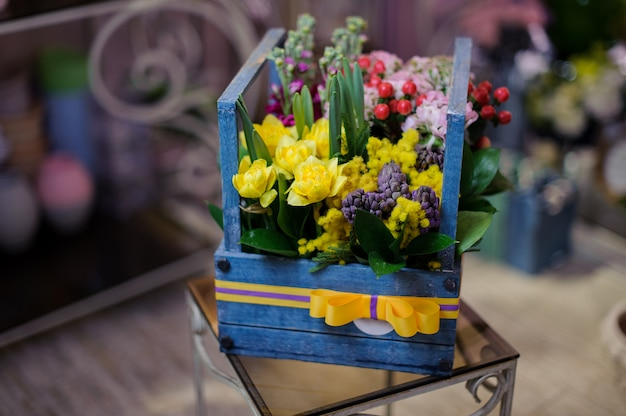 Linda caixa de madeira de flores vermelhas, brancas e amarelas, decoradas com folhas verdes e frutas vermelhas