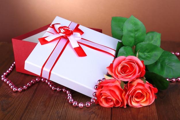 Linda caixa de presente com flores na mesa em fundo marrom