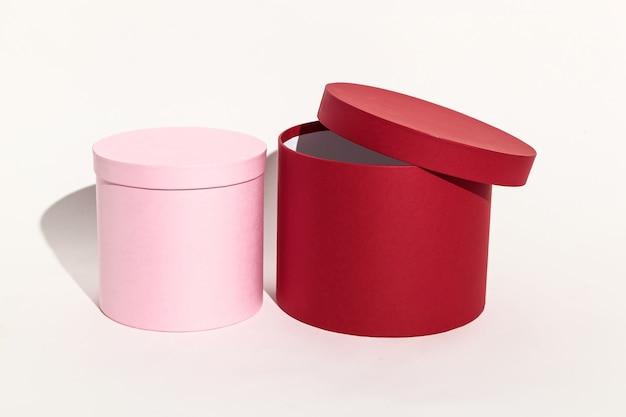Linda caixa de presente redonda rosa e vermelha para embalar uma surpresa com a tampa fechada
