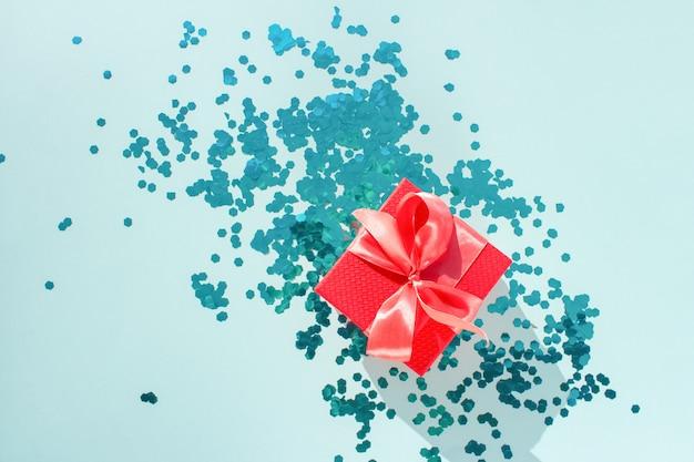 Linda caixa de presente vermelha amarrada com fita coral de cetim brilhante sobre fundo turquesa com confetes azuis brilhantes dispersos.