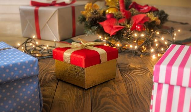 Linda caixa de presente vermelha com fita dourada no piso de madeira contra luzes brilhantes e árvore de natal. cenário perfeito para férias