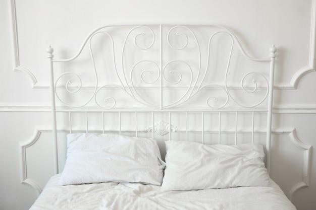 Linda cama de ferro forjado em um quarto branco