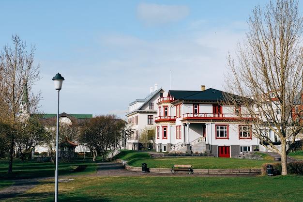 Linda casa branca de dois andares com telhado preto perto do parque em reykjavik