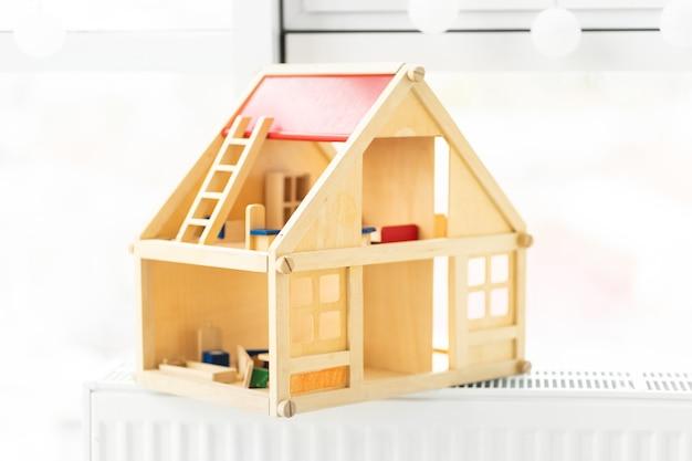 Linda casa de bonecas de madeira no fundo da sala de luz