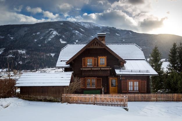 Linda casa de madeira tradicional nos alpes coberta de neve